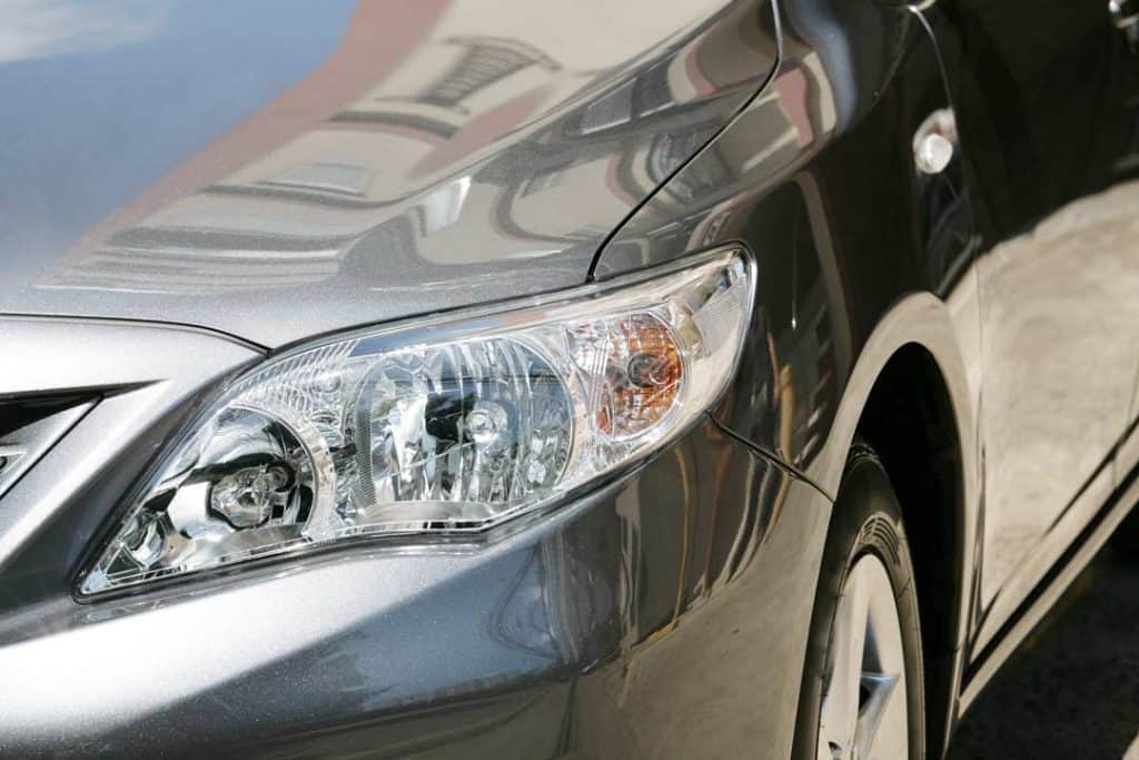 Image of a close up of the front fender and headlight of a luxury car