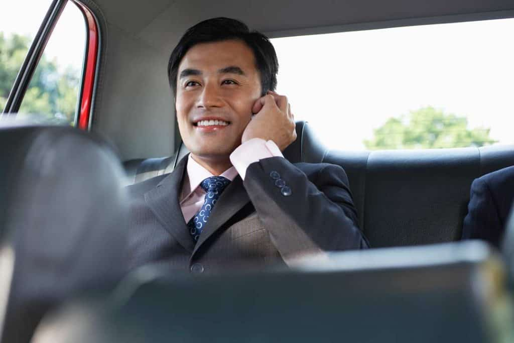 Image of relaxed and happy business man riding in the back of a luxury car while talking on his phone