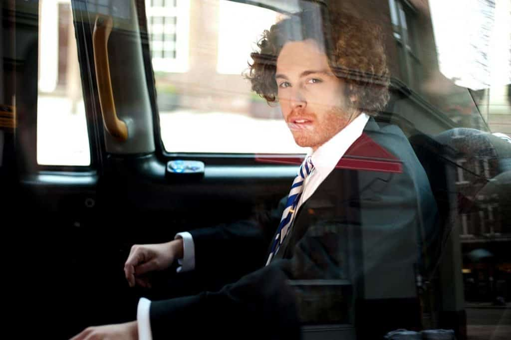 Young businessman in suit sitting in the back of a luxury car. He is looking out the side window while being drive to his destination