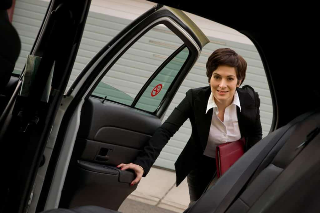 Business woman getting into back of luxury car service vehicle