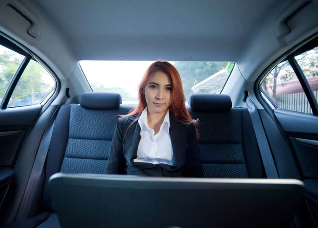 Image of a business woman on her laptop in the back of a luxury car